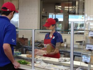 Kroger Marketplace employees work at the make-your-own-sandwich bar at the new store's pre-made meals section.