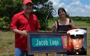 The parents of Marine Lance Cpl. Jacob Lugo hold a street sign on a road being dedicated in their son's honor. Lugo was killed in action in 2004 (Photo Credit: Bill Castleman; Military Times).