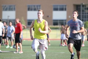"""Andrew Hopkins (yellow shirt) of Marcus High School takes part in one of fifty 40-yard dashes in what coaches call the """"final exam"""" of summer workouts on July 29."""