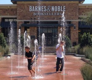 Kids play in the geysers Friday afternoon at The Shops at Highland Village.