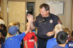 """Hilltop Elementary students greet Argyle ISD Police Chief Paul Cairney with high fives on """"Back The Blue"""" day."""
