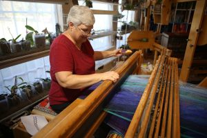 Master Weaver Gloria Haefner-Gatti of Double Oak at her giant loom. (Photo by Foust Photography)