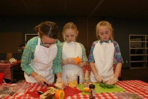 The Cookin' Cowgirls, Shea Hook, Kaylie Smith and Lydia Smith, prepare their dish for the Denton County 4-H Food Challenge.
