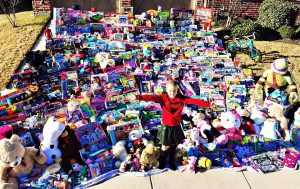 Sadie Keller of Lantana standing in front of the 1,276 toys she collected for kids in the hospital.