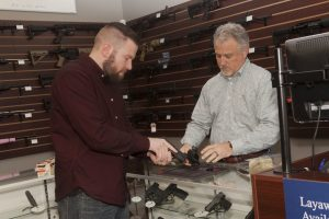 Travis Bond, owner of DFW Shooters Academy in Highland Village, (right) shows a customer some of his wares. (Photo by Helen's Photography)