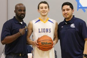 Coram Deo Academy Boys Basketball Head Coach Email Asante (left) and Assistant Coach Fonzo Martinez present Logan McClure with the game ball after he broke 1,000 points in a season.