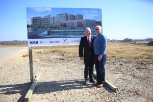 New Era Partners Scott Tarwater, president and CEO with Tim Lavender, founder and principal, with the rendering of Flower Mound's first hotel, The Courtyard of Marriott Hotels at the River Walk, being built by developer New Era Hotels and Resorts. (Photo by Foust Photography)