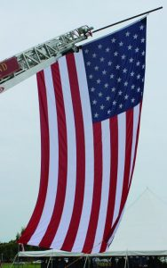 A huge American flag hung from a pole extending from a Flower Mound Fire Department truck. (Photo by Dru Murray.)