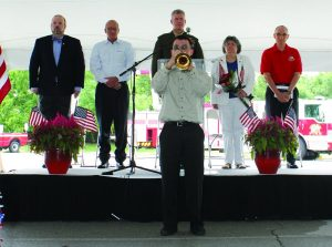 """Trumpeter Iver Sneva plays """"Taps"""" at the Flower Mound Memorial Day event. Standing behind him are (left to right) Mayor Pro Tem Kevin Bryant, Flower Mound Council Member Bryan Webb, Lt. Colonel Paul T. Patrick, and Flower Mound Fire Department Chaplain Russ McNamer. Photo by Dru Murray."""