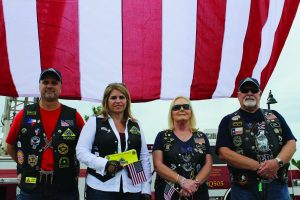 Old Glory serves as the background for Patriot Guard Riders (from l. to rt.) Brian Adams and Amy Weber of Lewisville and Sue and Howard Griffths of Flower Mound. The Patriot Guard motorcycle riders attend the funerals of fallen service members at the families' requests. Photo by Dru Murray.