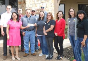Diana Corona, RSVP Executive Director, and Rhett Hubbard, RSVP board member, with Grande employees. (Photo: Grande Communications)