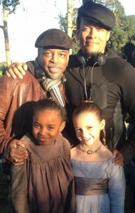 "Kiera Strauss, bottom right, as the young Missy with Saniyya Sidney in the role of Kissy are pictured with Executive Producer Levar Burton, who performed the role of Kunta Kinte in the original version of ""Roots"" in 1977, and Director Mario Van Pebbles, top right."