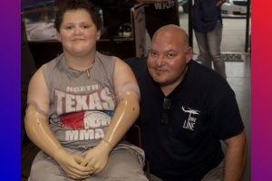 Memphis Lafferty, pictured with his father, Chris, received the gift of prosthetic hands to help him enjoy life to its fullest. (Photo by Helen's Photography)