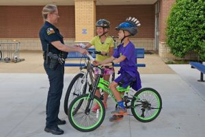 "A Flower Mound police officer ""tickets"" kids with a 7-Eleven Operation Chill coupon for being safe by wearing helmets while riding their bikes."