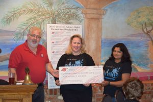 Dana Marshall and Luna Bhaskar of McKamy Robotics Club accept a $500 donation from Summit Club of Flower Mound president Claudio Forest.