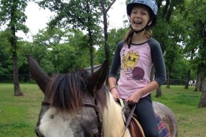 Kathryn, a client of Unbridled Horse Therapy in Flower Mound, enjoys her time in the saddle.
