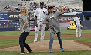 Debbie Sardone, (left) founder of Cleaning for a Reason, throws out the first pitch at a New York Yankees baseball game on June 7. Sardone is pictured with Marybell Ruiz, a cancer patient and mother of two.