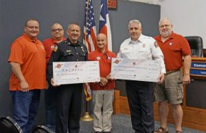 During the Flower Mound Town Council meeting on July 18, the Summit Club of Flower Mound presented checks for $1,000 to the FMPD and FMFD. Pictured, left to right, are: Summit Cub members Perfecto Solis, Paul Stone, Al Picardi and Claudio Forest; with FMPD Chief Andy Kancel and FMFD Chief Eric Greaser holding their checks. (Photo courtesy of Molly Fox)