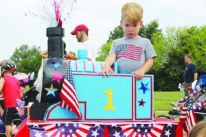 """Oliver Breeden, 2, of Flower Mound, is serious about being the engineer of his Fourth of July Thomas the Tank engine his grandfather Keith Johnson constructed for him. """"It was repurposed for the parade,"""" said Oliver's mother Aimee. Photo by Dru Murray."""
