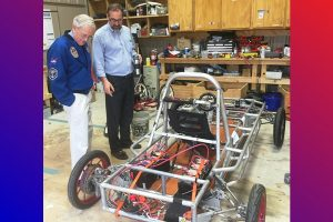 Astronaut Charlie Duke (left) learns more about Liberty's solar car from Dr. Brent Dragoo on his visit to the school in April.