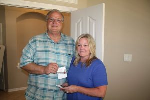 Argyle Fire Chief Mac Hohenberger and wife, Karla, accept a gift card from Brightside Boutique in The Shops at Highland Village to help replace the clothes they lost in a house fire on June 21st.