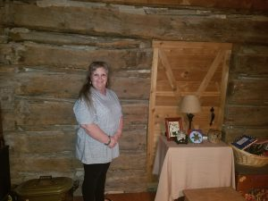 Tami Lynch Peevey standing in front of the log cabin wall in her living room. (Courtesy Photo: Ronnie Peevey)