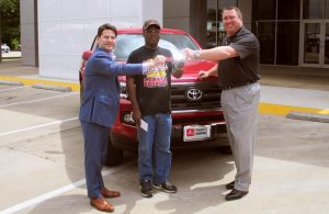 Don Moody (center) bought a ticket for the Community Support Raffle and won a 2016 Toyota Tacoma from Toyota of Denton.