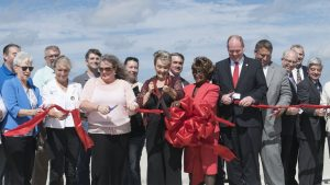 Denton County Commissioner Bobbie Mitchell holds the red ribbon as local and state officials, engineers and project heads of the 35Express Project give it a snip to signify the opening of the new bridge over Lewisville Lake. County Judge Mary Horn wields the big scissors. (Photo by Christina Ulsh/Lewisville Texan Journal)