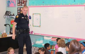 Flower Mound Police Officer Erik White talking to second graders in Sarah Strange's class on Career Day at Garden Ridge Elementary School in Flower Mound.